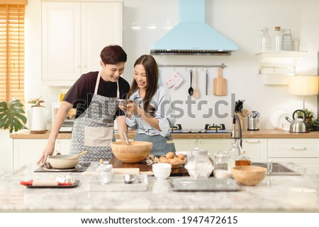 A couple uses their smart phone to take a picture while admiring his wife's cooking work With a happy face in an atmosphere of love