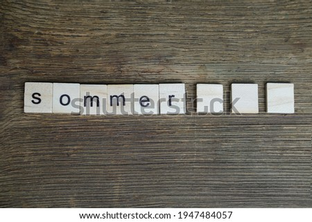 word summer in German is made up of volumetric letters on wooden background, white starfish, concept of summer time, vacation time, travel, boat trip, beach impressions