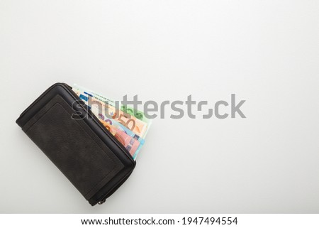 Black leather wallet with euro money on light gray table background. Empty place for text.