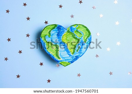 Drawn planet Earth in the shape of a heart among the stars on a blue background. Environmentally friendly World map. Earth Day, 22 april.