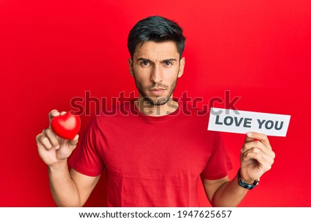 Young handsome man holding red heart and love you message skeptic and nervous, frowning upset because of problem. negative person.