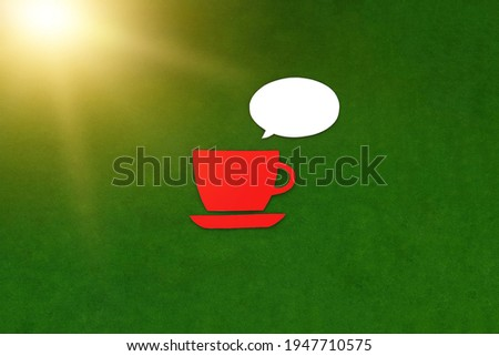 Red coffee cup, white oval for negotiations on a green background. Lunch break, conversation at the table.