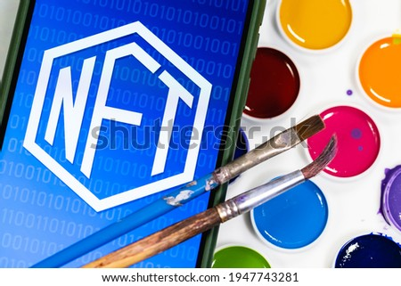 A NFT (non-fungible token) is a special crypto token that uses blockchain technology to link with a unique digital asset. NFT symbol on the background of watercolors and two paintbrushes.