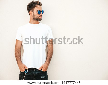 Portrait of handsome smiling stylish hipster lambersexual model.Man dressed in white T-shirt. Fashion male posing in the street in sunglasses  Royalty-Free Stock Photo #1947777445