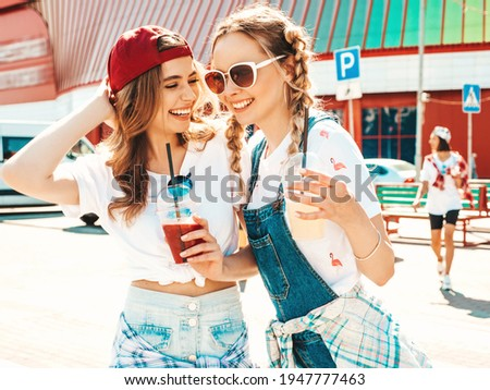 Two young beautiful smiling hipster female in trendy summer clothes.Sexy carefree women posing outdoors.Positive models holding and drinking fresh cocktail smoothie drink in plastic cup with straw Royalty-Free Stock Photo #1947777463
