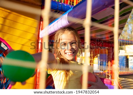 A funny girl sits in a playground with soft and bright equipment and throws colorful balls towards the camera while enjoying the warm summer sun Royalty-Free Stock Photo #1947832054