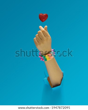 K pop concept. A girl hand with rainbow pyramid studded bracelet showing fingers heart gesture. Red glittery heart above. Optimistic blue in background.