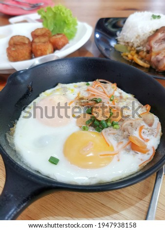 Indochina pan-fried eggsis  fried egg topping with bacon and chinese sausage in hot pan, very famous in north eastern Thailand and Vietnam.   Royalty-Free Stock Photo #1947938158