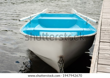 A blue and white boat with oars stands on the water at a wooden pier Royalty-Free Stock Photo #1947942670
