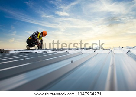 Builders in work clothes install new roofing tools, roofing tools, electric drill and use them on new wooden roofs with metal sheets  Royalty-Free Stock Photo #1947954271