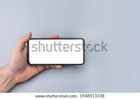 Mockup cell phone. male hand holding phone horizontally with blank white screen. Mockup phone horizontal. human left hand holding black horizontal mobile phone Royalty-Free Stock Photo #1948013338