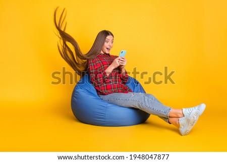 Full size profile photo of optimistic brunette long hairdo lady hold telephone wear shirt jeans sit on bag isolated on yellow background