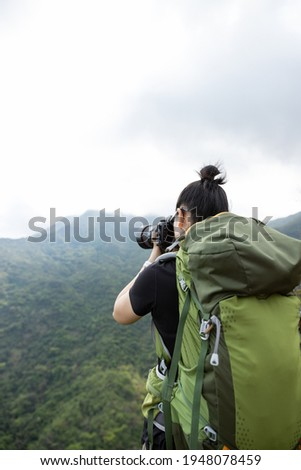 Woman photographer taking pictures in spring mountain