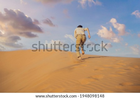 The person overcomes difficulties and aspires to the purpose and dream. A man overcomes difficulties in life as if in a desert Royalty-Free Stock Photo #1948098148