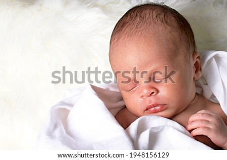 baby  wrapped up in white blanket just been cared for after having a good sleep in bed stock photo