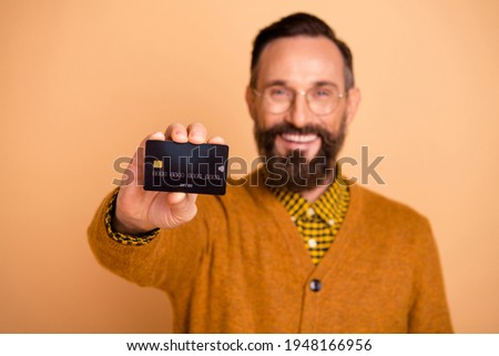 Photo of positive mature man show credit card in camera isolated over beige color background