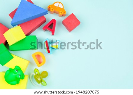 Children's background. Toys for baby that develop hand motor skills, thinking. Soft multi-colored constructor, figures of car, boat, rubber frog, letters, pacifier on blue background. Space for text.