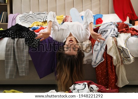Young woman surrounded by different clothes in messy room. Fast fashion concept Royalty-Free Stock Photo #1948221292