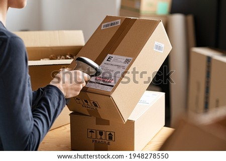 Hands scanning barcode on delivery parcel. Worker scan barcode of cardboard packages before delivery at storage. Woman working in factory warehouse scanning labels on the boxes with barcode scanner. Royalty-Free Stock Photo #1948278550