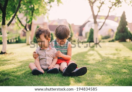 Two brothers, a baby and a toddler, sitting together on grass #194834585