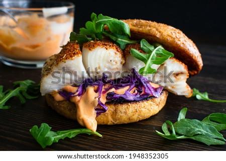 Blackened Fish Burger and Sriracha Mayo: A halibut fish sandwich with red cabbage and arugula on a whole wheat brioche bun