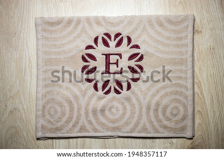 Embroidery design, alphabet monogram E. Machine Embroidery on a cotton towel with burgundy color.