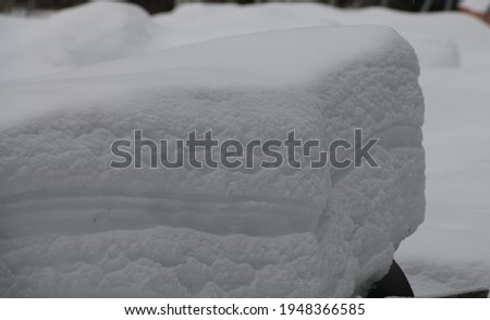 large block of white snow and frozen ice showing different layers of thickness and weight of snowfall in winter and spring thaw avalanche detection layered like a cake horizontal format room for type