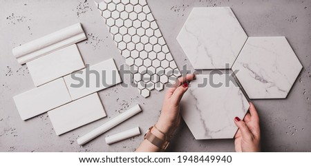 Interior design and home decoration - different shapes of white ceramic and gres tiles. Designer choosing bathroom or kitchen renovation materials. Captured from above (top view, flat lay). Royalty-Free Stock Photo #1948449940