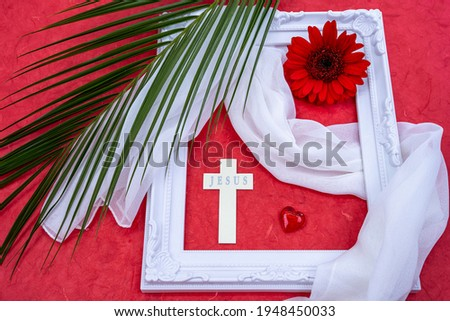 Decoration with the Jesus cross, white picture frame, palm branch and gerbera flowers. Template for Easter greeting card, postcard, poster.