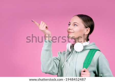 Thoughtful smiling woman, a student about to study, with a backpack and with headphones. Portrait on a solid monochrome pink background. The female shows with her index finger, copy space