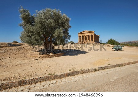 Temple of Concordia, or Tempio della Concordia in Italian. Barren landscape with a single olive tree and statue of Ikarus. Valley of Temples, Agrigento, Sicily, Italy.