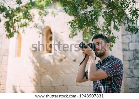 A man with a camera near the old temple. Tourist photographer takes pictures of attractions near the ancient stone wall of a castle or temple
