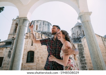 Young couple makes selfie on the background of an ancient temple on a sunny day. Lovers take pictures near the ancient stone walls of the church