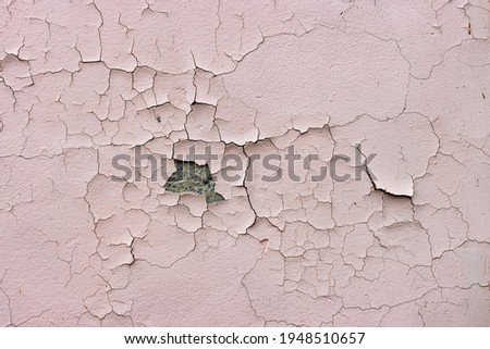 Close-up. Badly fixed building facade wall covered with cracks in stucco and paint. A big patch of stucco missing in the middle exposing the cement coat brown coat, rest is cracked and peeling. Royalty-Free Stock Photo #1948510657