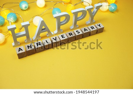 Happy Anniversary alphabet letter with LED cotton balls on yellow background Royalty-Free Stock Photo #1948544197