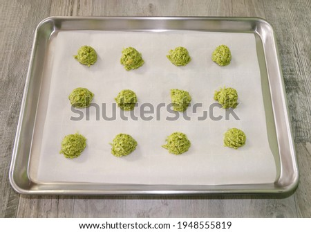 A baking sheet with scoops of guacamole chips mix . Step for making keto guacamole chips.