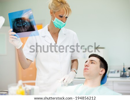 Female dentist showing x-rays to her patient. Male patient at the dentist's. #194856212