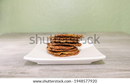 Guacamole chips stacked on a small white plate.