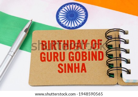 Holidays in India. Against the background of the flag of India lies cardboard with the inscription - Birthday of Guru Gobind Sinha