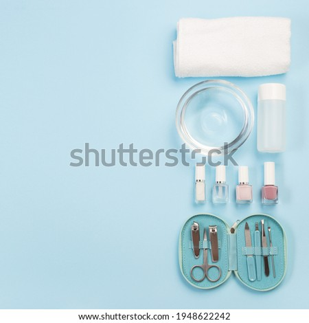 Spa set, manicure or pedicure equipment with nail coat or polish, on a blue background, top view, copy space, square format