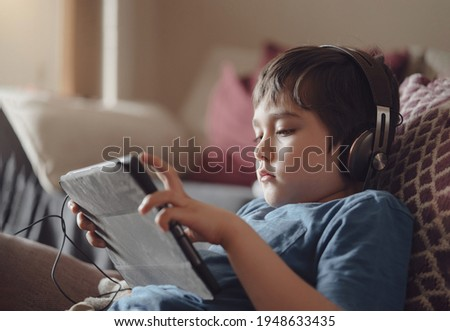 Authentic portrait Kid sitting on sofa watching cartoons on tablet,Yong boy playing game on touch pad, Child lying on couch wearing headphoes listening to music or relaxing on his own in living room