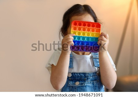 Cute faceless child playing with the Pop It fidget. Push pop bubble flexible fidget sensory toy provide discharge and are good for the development of kid. Selective focus on toy. Royalty-Free Stock Photo #1948671091