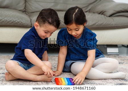 Two cute children playing with the Pop It fidget. Push pop bubble flexible fidget sensory toy provide discharge and are good for the development of kid. Soft focus. Royalty-Free Stock Photo #1948671160
