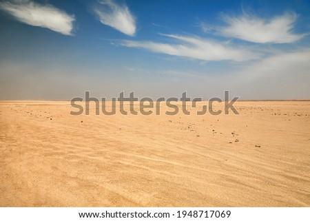 Dry desert landscape. Hot lifeless sand of desert and blue sky in summer sunny day. Flat desert of Egypt. Travel and tourism concept. Royalty-Free Stock Photo #1948717069