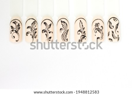 Nail design on nail tips Monogram patterns in black gel paint on a beige background. Space for text