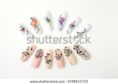 Nail design on nail tips Monogram patterns drawn with black gel paint. Space for text