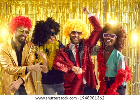 Happy people dancing gangnam style on stage with shiny golden background. Group of friends disguised in boas, glasses, sequin jackets and funny silly curly wigs having fun at night club disco party Royalty-Free Stock Photo #1948901362