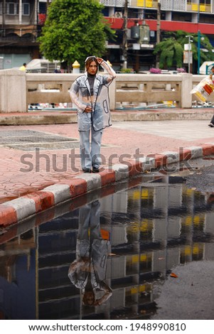 Young Asian Woman stand along walkway and puddle dirty water on street after raining. girl wear clear fashion rain coat with reflect on road