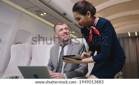 Airplane Stewardess Sending Digital tablet choose food order service on the plane flight, Business class. Flight Attendant Shows Tablet Computer with Menu to Caucasian Male Passenger. They're Inflight Royalty-Free Stock Photo #1949013883