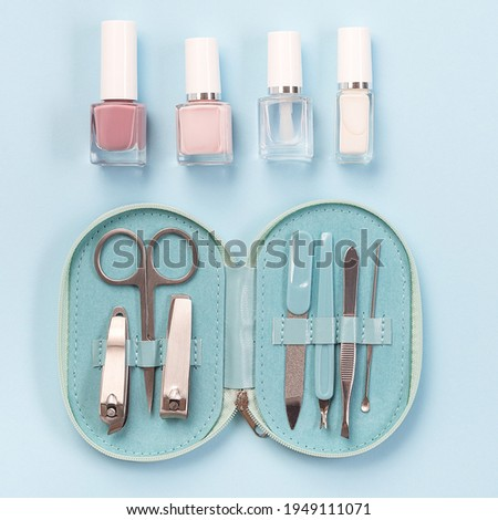 Spa set, manicure or pedicure equipment with nail coat or polish, on a blue background, top view, square format